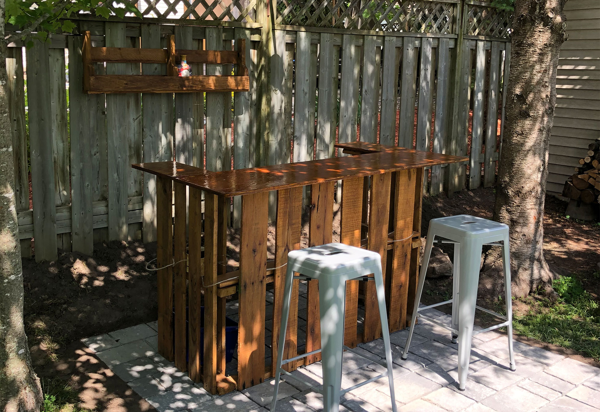 Make a Backyard Bar Using Pallets. Backyard bar made out of pallets with two bar stools in front of it.