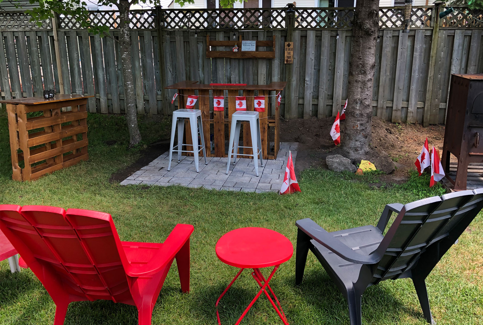 A view of the author's back yard showing some outdoor chairs, the bar, shelf and pub table.