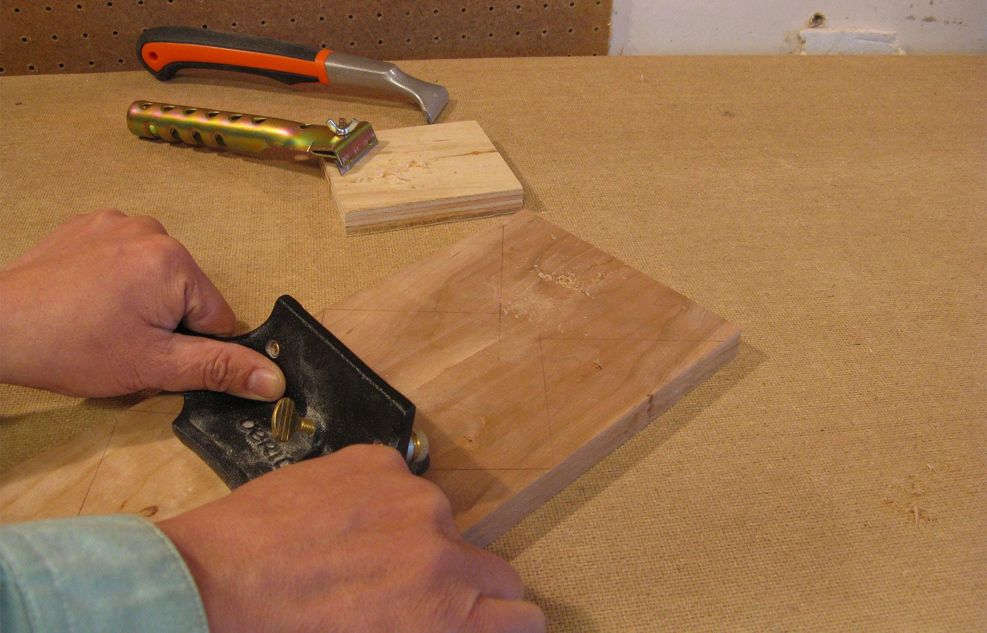 Scraping off glue squeeze-out using a cabinet scraper.