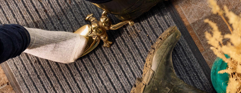 Jardinier utilisant un coléoptère tire-botte en laiton pour enlever ses bottes avant d'entrer dans la maison