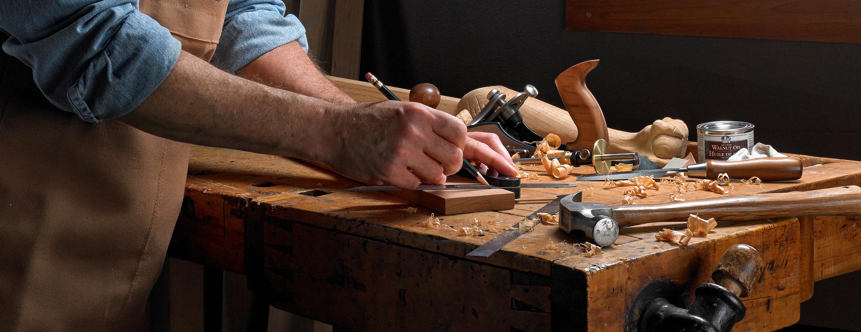 Un menuisier utilise une équerre combinée pour tracer une ligne à 45⁰ sur une pièce de bois. Divers outils et fournitures pour le travail du bois sont à proximité sur l'établi.